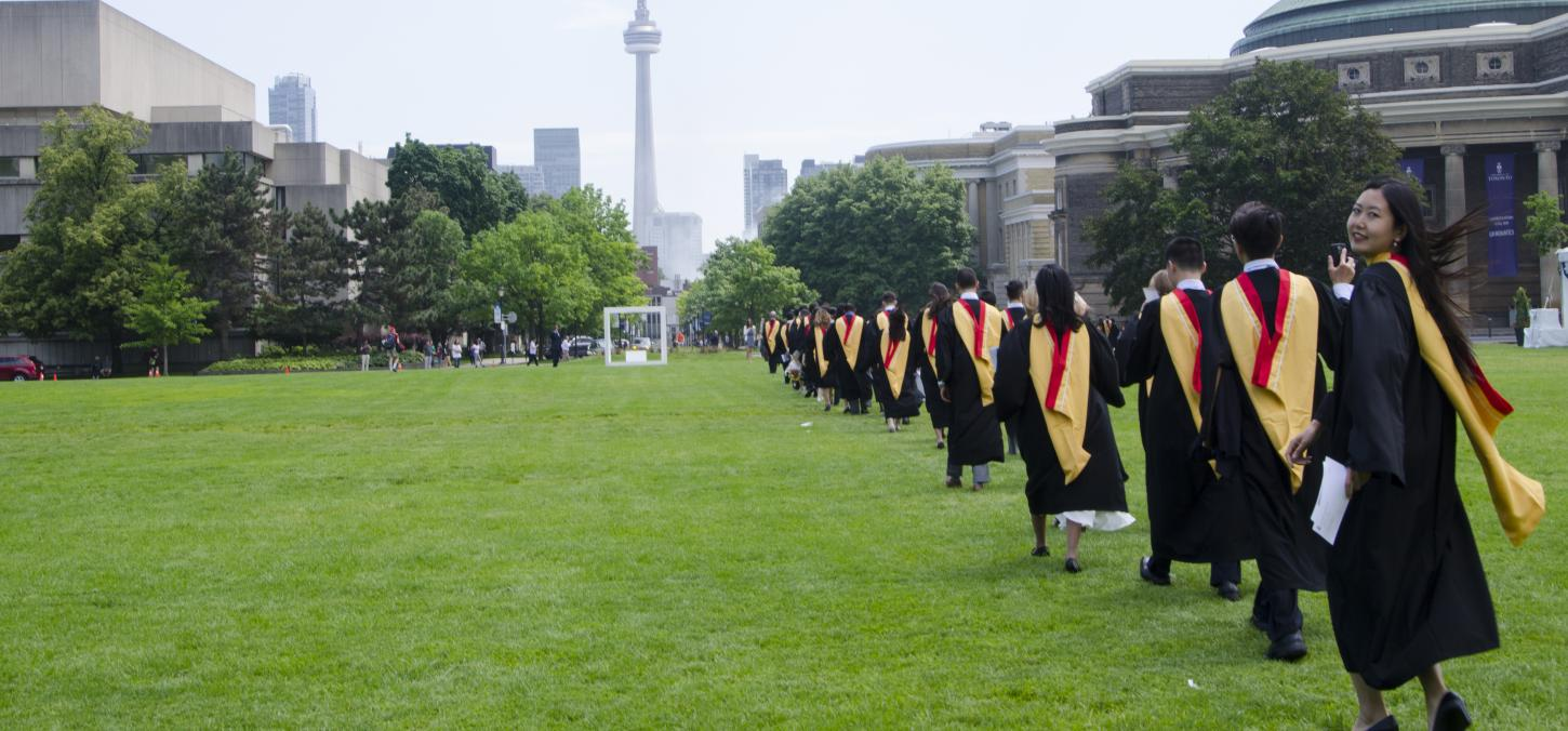 student procession to convocation hall 2017, one woman looks back