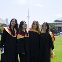 four femaie students in gowns stand on commons, CN tower in the background